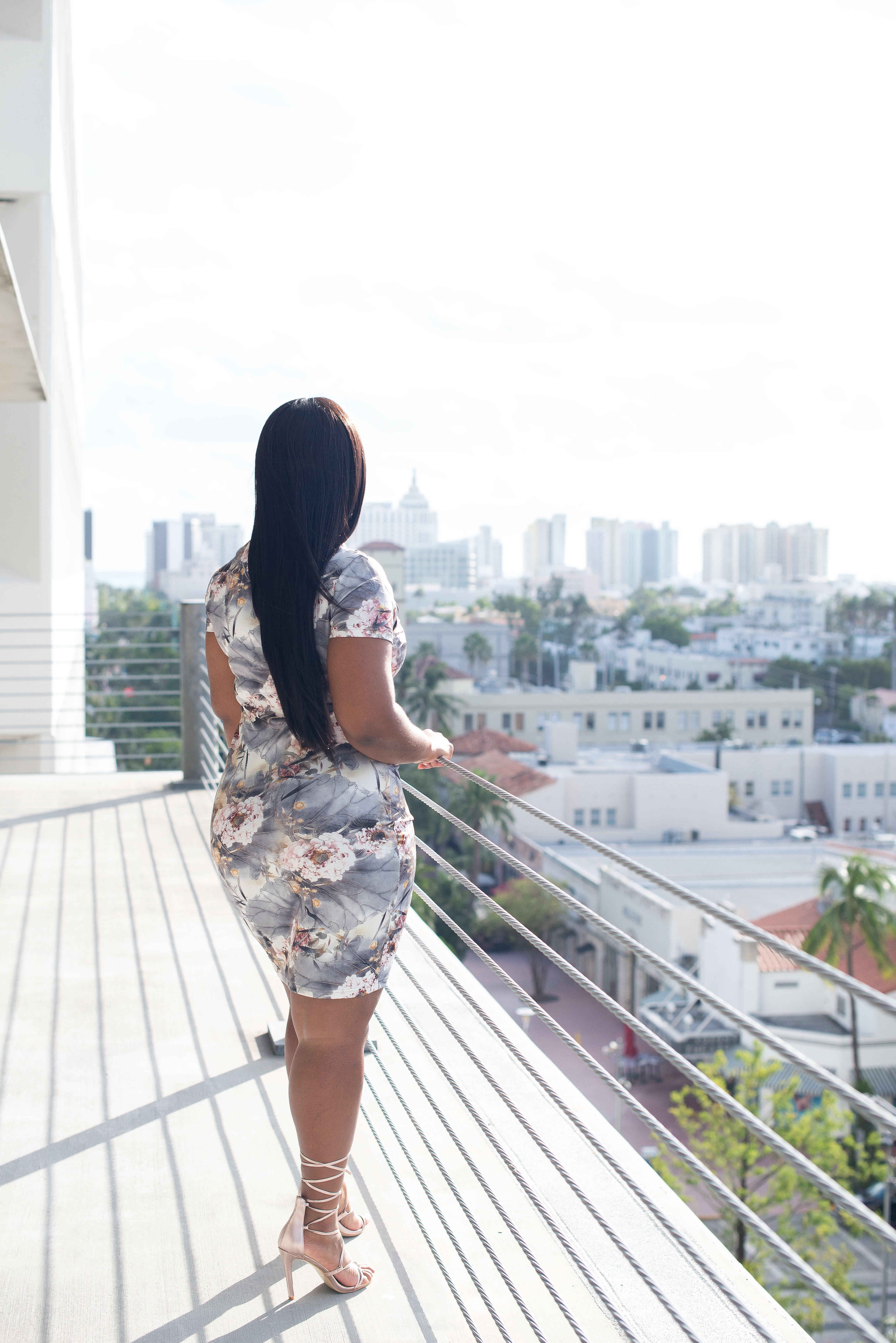 Black blogger with long hair wearing quipao and Simmi Shoes Heels overlooking Miami Beach