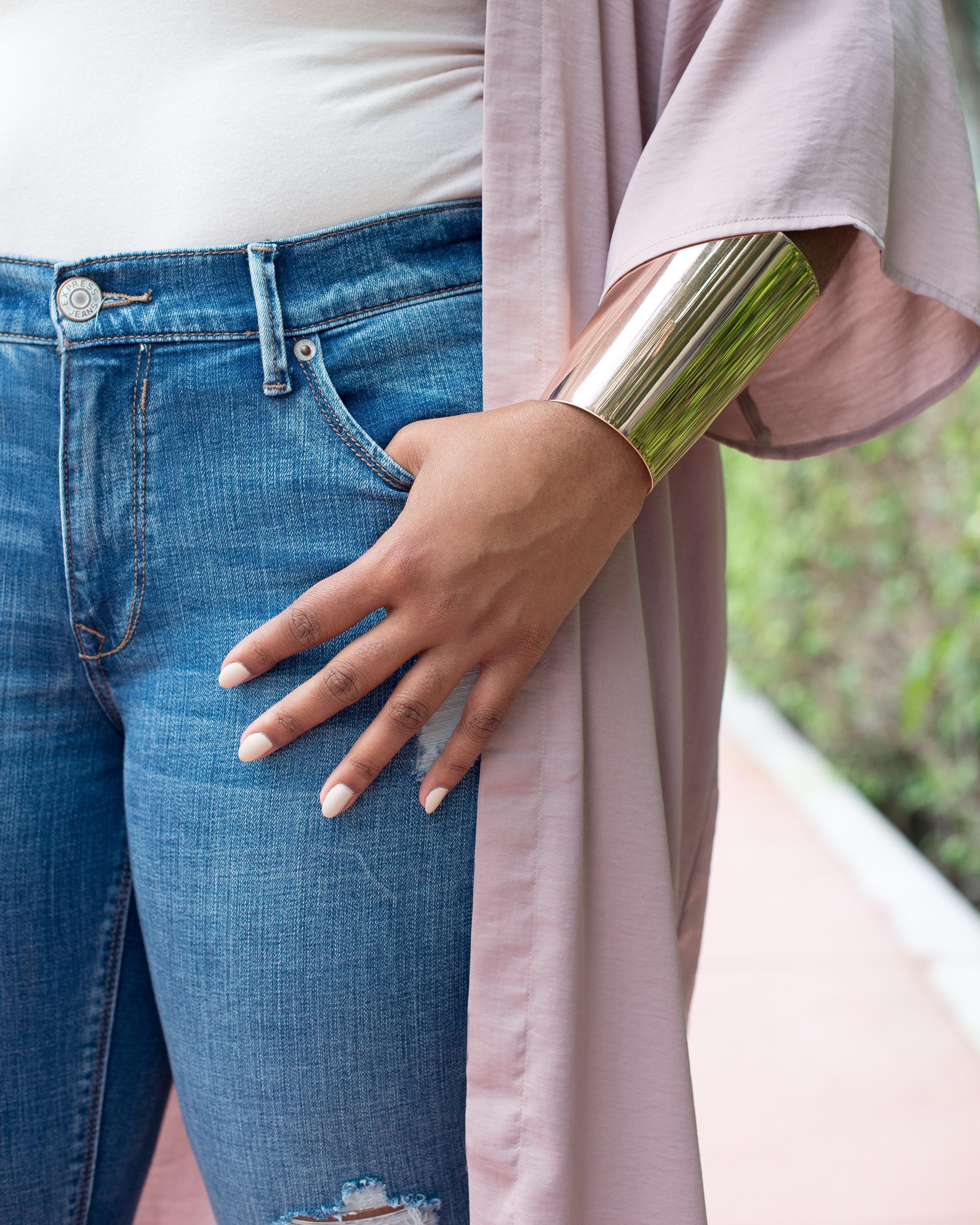Closeup of Black blogger's rose gold arm cuffs and blush pink Forever 21 kimono