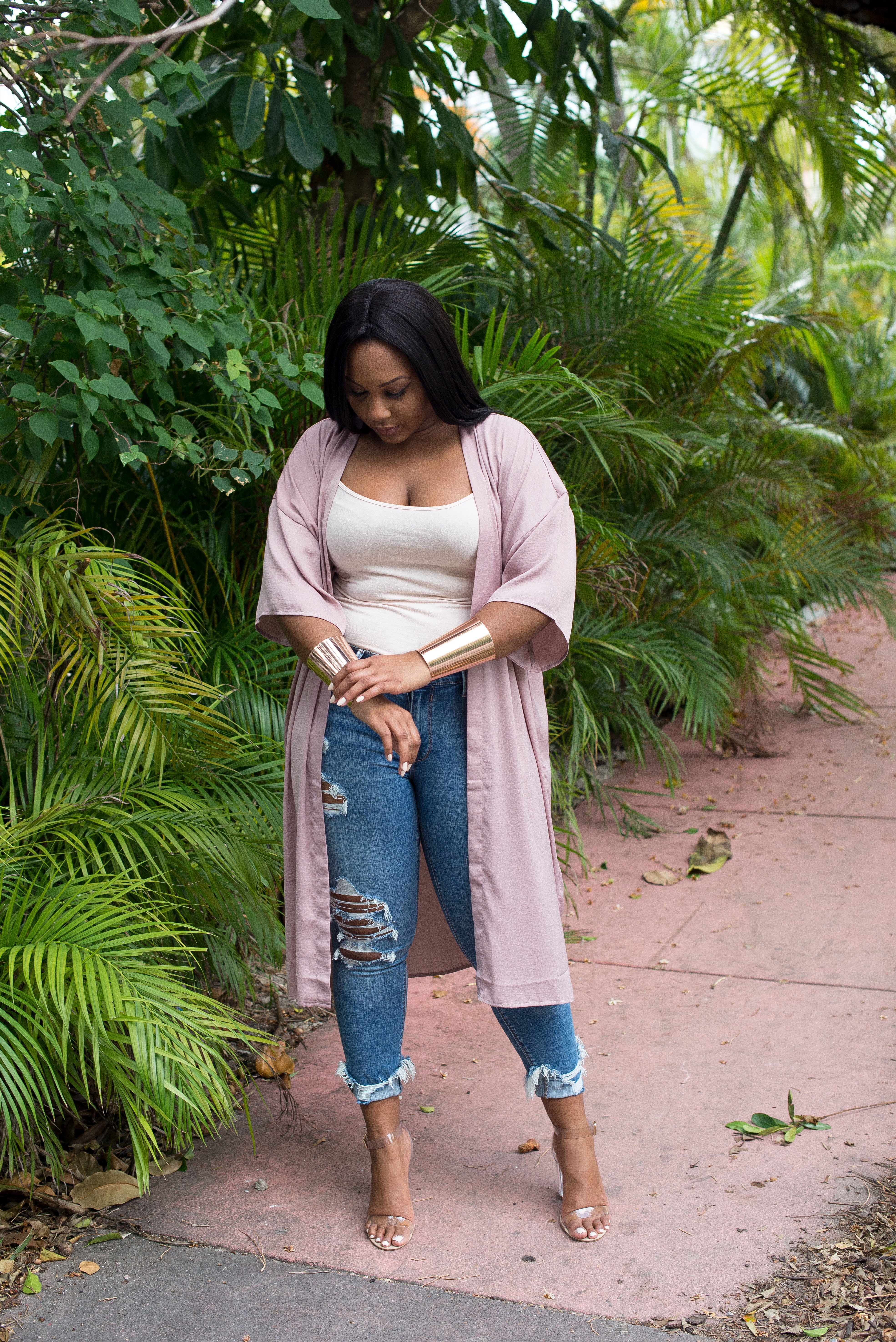Fashionable black blogger wearing Forever 21 blush pink kimono, rose gold accessories, Express Jeans, and clear heels