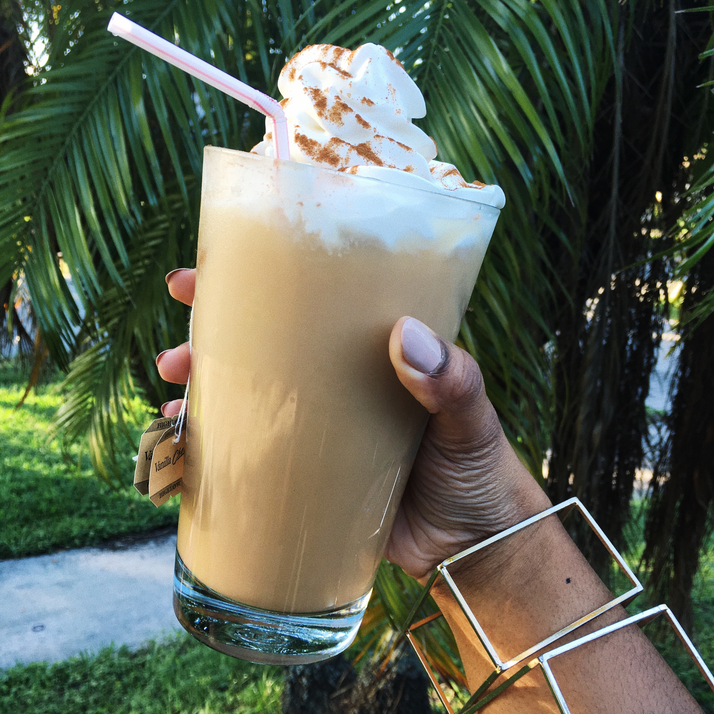 Black woman with gold geometric bracelets holding glass of Bigelow Vanilla Chai Tea with straw topped with whipped cream and cinnamon