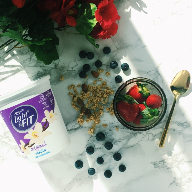 Flatlay of granola, chopped strawberries, Dannon Light & Fit vanilla yogurt and blueberries on a marble counter top.