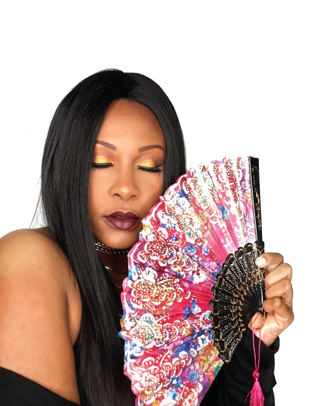 Beautiful black lifestyle blogger wearing Juvia's Place Nubian 3 Palette holding paper fan