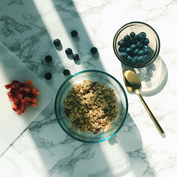Flatlay of granola, chopped strawberries, and blueberries on a marble counter top.