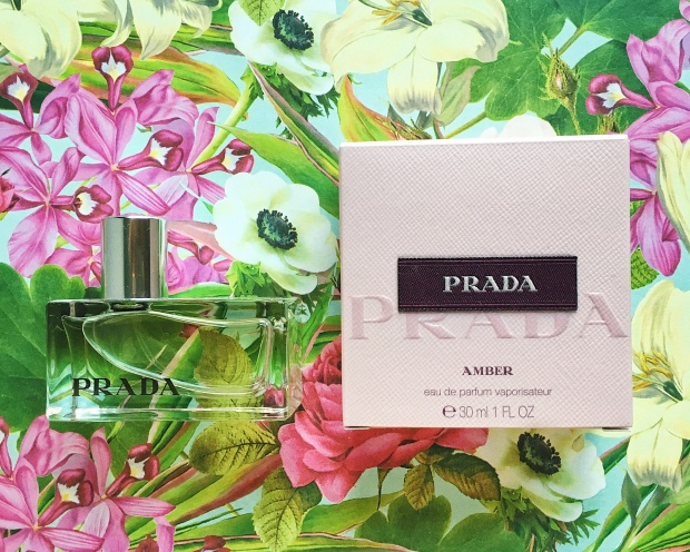 Prada Amber flatlay with a tropical flower scape