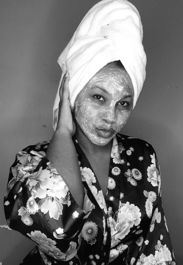 Black and white photo of black lifestyle blogger wearing Origins face mask wearing a silk robe