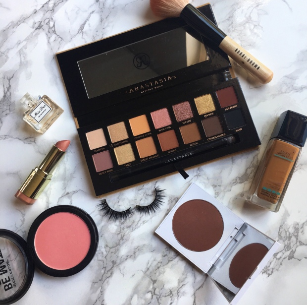 Flatlay with Anastasia Beverly Hills Soft Glam Palette, Bobbi Brown Brush, Colourpop Cosmetics Bronzer, Milani Lipstick, Huda Beauty Lashes and Blush